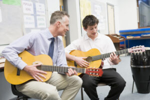 Schoolboy and teacher playing guitar in music class